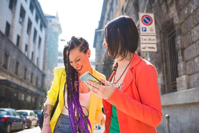 Mujeres en descanso urbano usando teléfono móvil, Milán, Italia - foto de stock