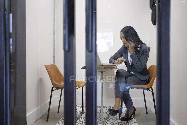 Businesswoman using laptop and making telephone call — Stock Photo
