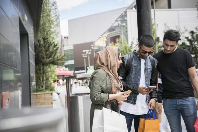 Tres amigos de pie en la calle mirando el teléfono inteligente - foto de stock