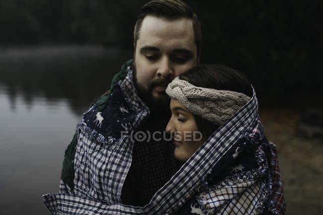 Пара, завернутая в одеяло, обнимающая озеро — стоковое фото