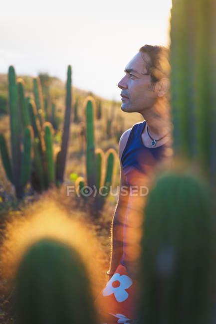 Mature man looking at view by cacti, Jericoacoara National Park, Ceara, Brazil — Stock Photo