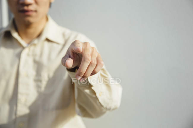 Mid section of young man pointing at camera — Stock Photo