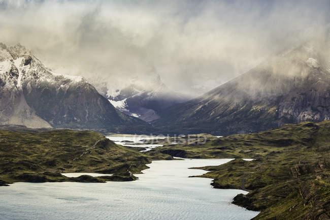 Низькі хмари та сонце промені в гірській річці краєвид, Торрес дель Пайне Національний парк, Чилі — стокове фото