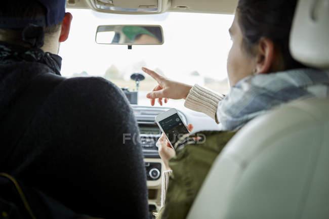 Молодая пара в машине во время женщина Холдинг смартфон и указывая направления — стоковое фото