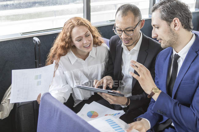 Businessmen and woman looking at digital tablet on passenger ferry — Stock Photo