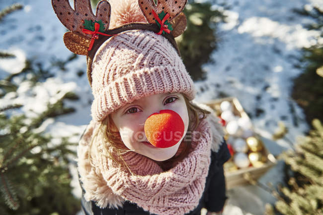 Girl in christmas tree forest with red nose, high angle portrait — Stock Photo