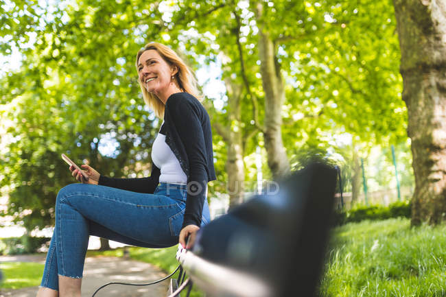 Woman using smartphone in city park — Stock Photo