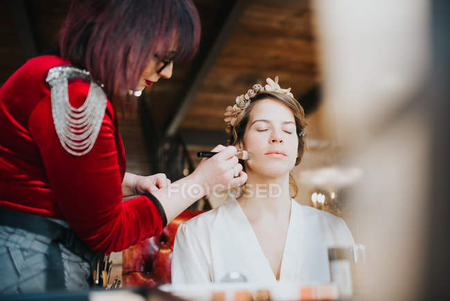 Bride preparing for wedding with make up artist — Stock Photo