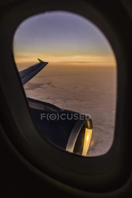 Pôr do sol paisagem nublada e asa do avião através da janela do avião — Fotografia de Stock
