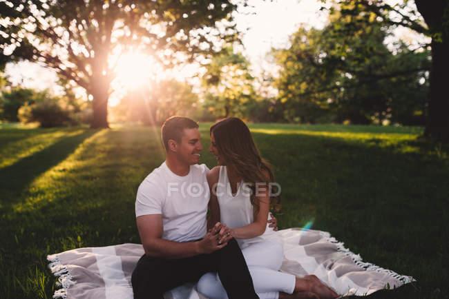 Романтическая молодая пара, сидящая в парке, держась за руки на закате — стоковое фото