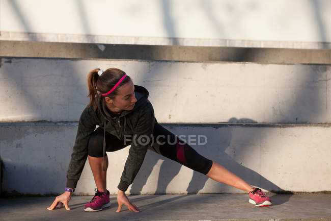 Young woman warming up and stretching legs — Stock Photo