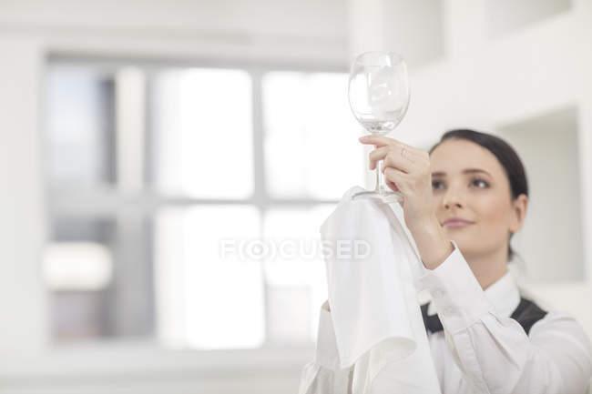 Официантка полирует бокал вина в ресторане — стоковое фото