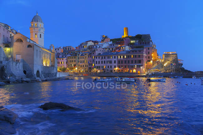Cliff side fishing village illuminated at dusk, Vernazza, Liguria, Italy, Europe — стоковое фото