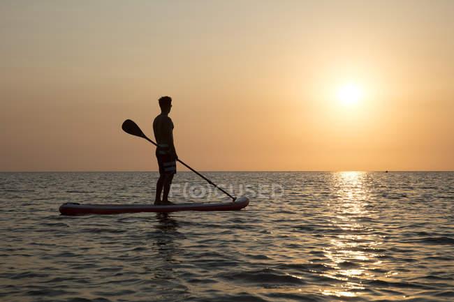 Silhouette d'homme debout sur paddleboard au coucher du soleil — Photo de stock