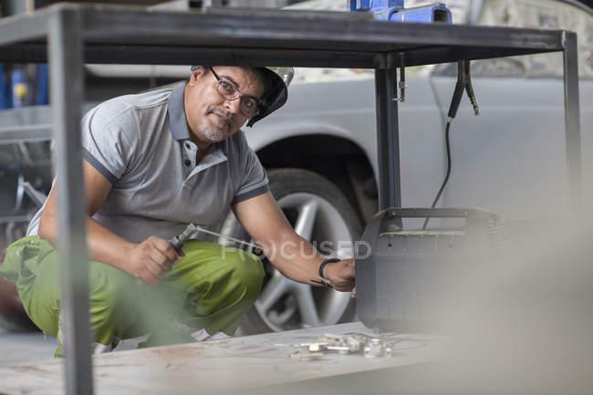 Welder  at work in bodywork repair shop — Stock Photo