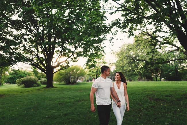 Romantisches junges Paar schlendert Händchen haltend im Park — Stockfoto