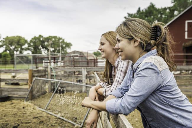 Zwei junge Frauen mit Blick vom Ranch Zaun, Bridger, Montana, Usa — Stockfoto