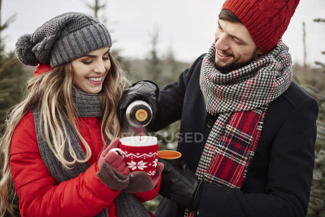 Young couple pouring coffee while shopping for christmas tree from forest — Stock Photo