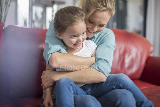 Мать и дочь на диване обнимаются и улыбаются — стоковое фото