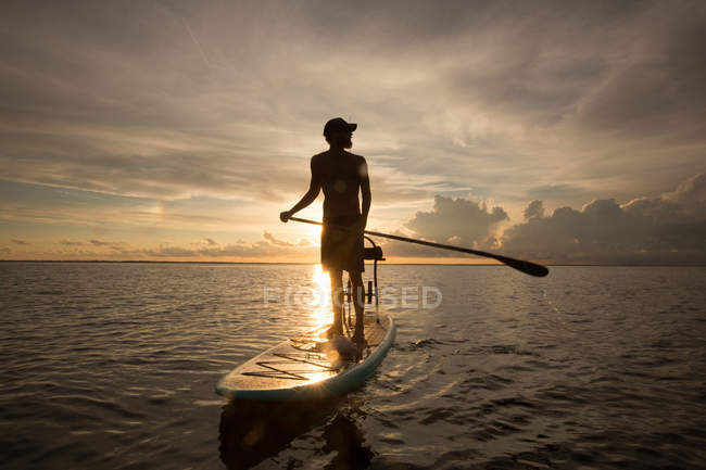 Man standing on paddle board in water, at sunset — Stock Photo