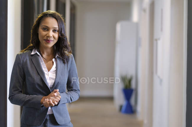 Portrait of businesswoman in office hallway smiling at camera — Stock Photo