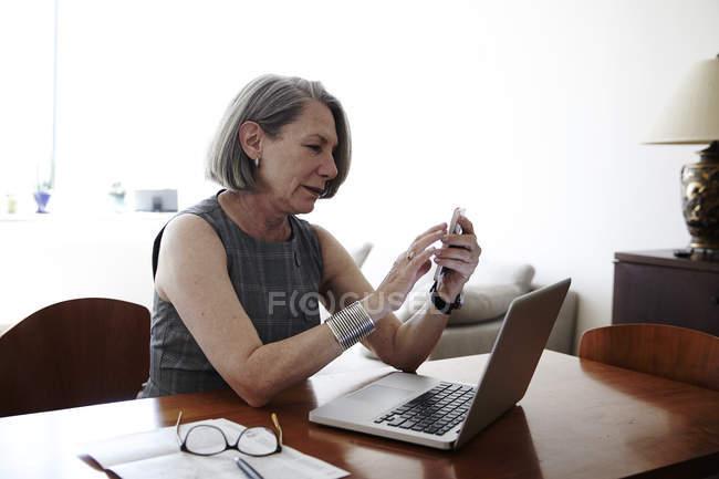 Старший підприємець, сидячи за столом, ноутбук перед нею, за допомогою смартфона — стокове фото