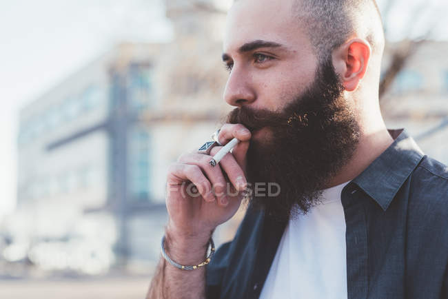 Portrait of young bearded man smoking — Stock Photo