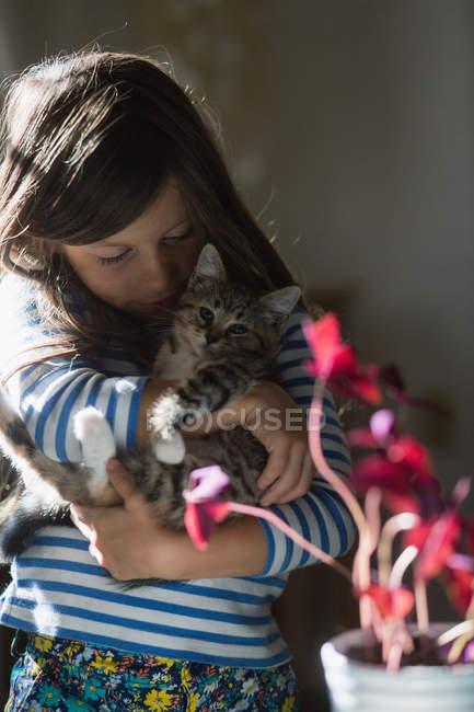 Portrait of girl in sunshine holding kitten — Stock Photo