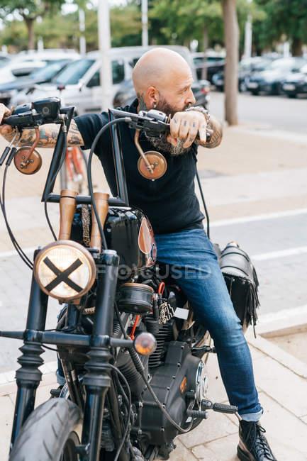 Hipster hombre maduro a horcajadas sobre la moto, mirando sobre su hombro - foto de stock
