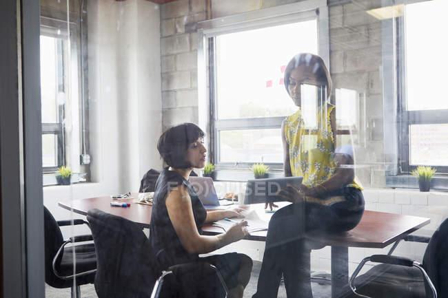 Deux femmes travaillant ensemble dans la salle de réunion et à l'aide de tablette numérique — Photo de stock