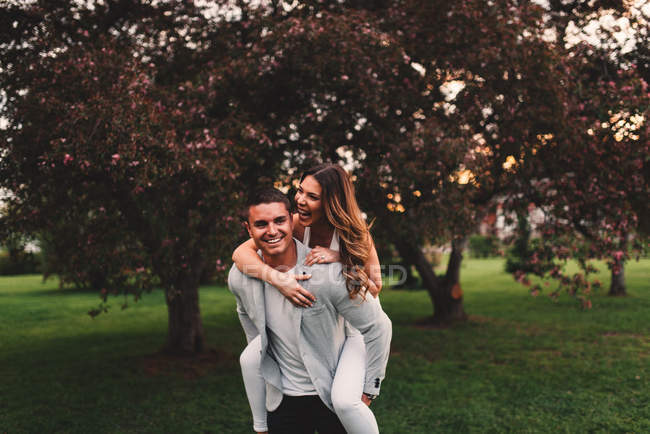 Молода людина, даючи подруга piggyback у парку у сутінках — стокове фото