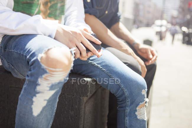 Dos amigos varones sentados al aire libre, usando vaqueros rasgados sosteniendo el teléfono inteligente, sección media - foto de stock