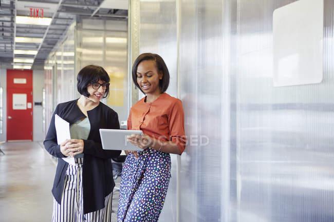 Two businesswomen looking at digital tablet in office corridor — Stock Photo