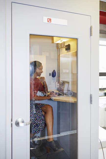 Mulher na cabine telefônica do escritório usando laptop para chamada de vídeo — Fotografia de Stock