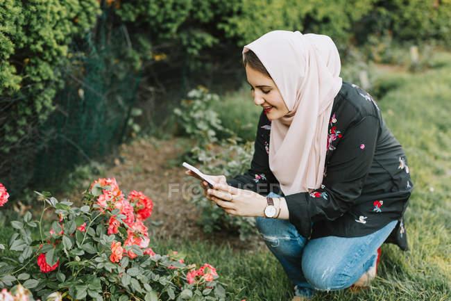 Mujer joven en hijab tomando flores de fotos en el teléfono inteligente - foto de stock