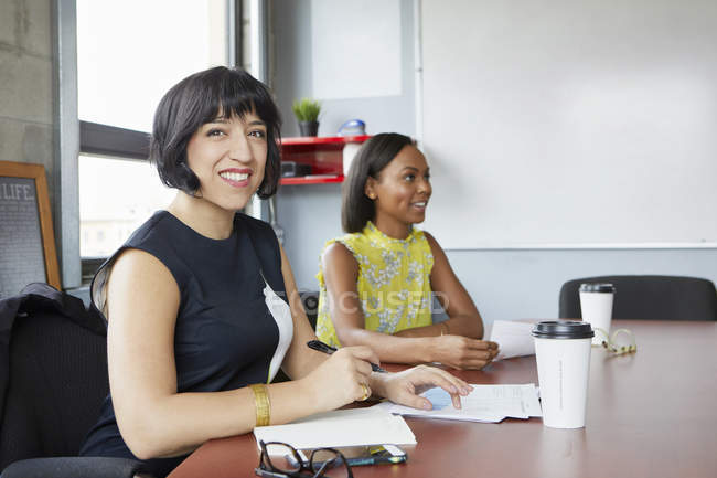 Two women sitting at meeting room table — Stock Photo