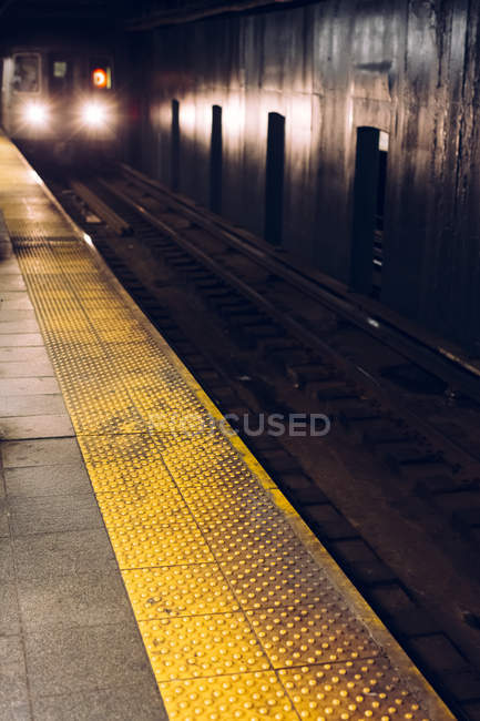 Subway train with headlights arriving at subway platform, Times Square, New York, USA — Stock Photo