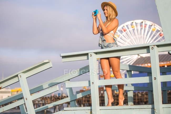 Young woman taking photographs from beach hut, Santa Monica, California, USA — Stock Photo
