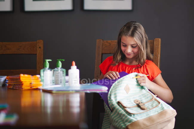 Girl packing backpack with school stationery supplies — Stock Photo