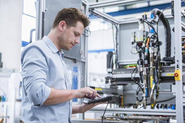 Lavoratore premendo il panello di controllo per macchinari di fabbrica — Foto stock