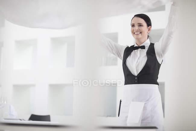 Официантка в ресторане, укладка скатерть — стоковое фото