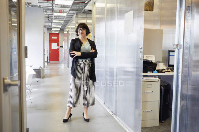 Portrait of businesswoman standing in office corridor — Stock Photo
