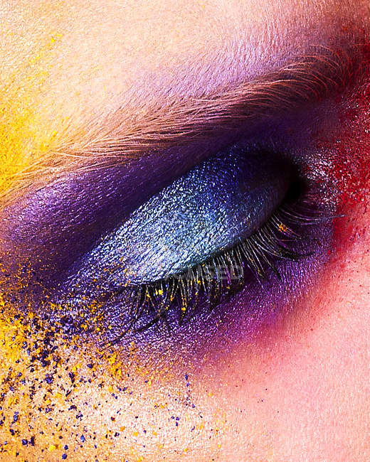 Close up of woman eye with colored powder eye shadow — Stock Photo