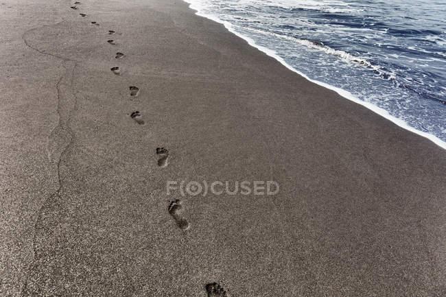 Следы на песке на побережье, Сан-Филипе, Фого, Кабо-Верде, Африка — стоковое фото