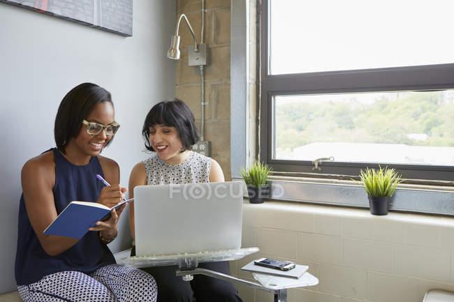 Две деловые женщины, работающие с ноутбуками и ноутбуками в современном офисе — стоковое фото