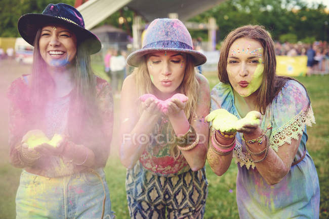 Three young women blowing colored chalk powder at festival — Stock Photo