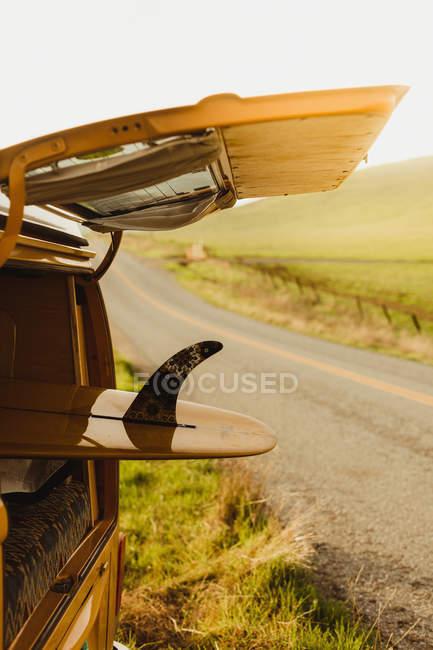 Bota de surf amarilla en vehículo recreativo vintage en carretera, Exeter, California, EE.UU. - foto de stock