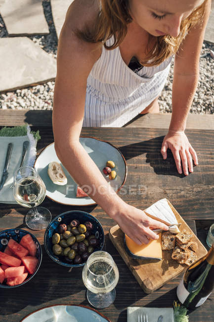 Young woman outdoors slicing cheese from cheeseboard — Stock Photo