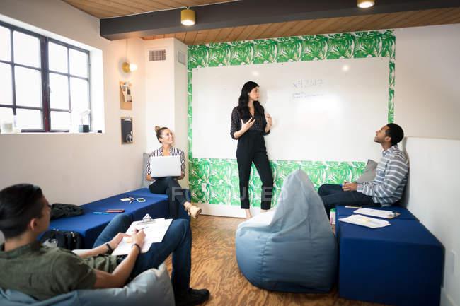 Collègues de travail avec le tableau blanc dans la salle de réunion créative — Photo de stock