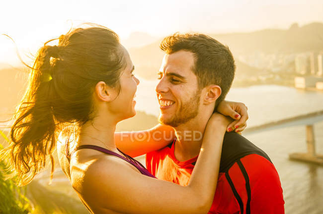 Young couple hugging and smiling to each other outdoors — Stock Photo